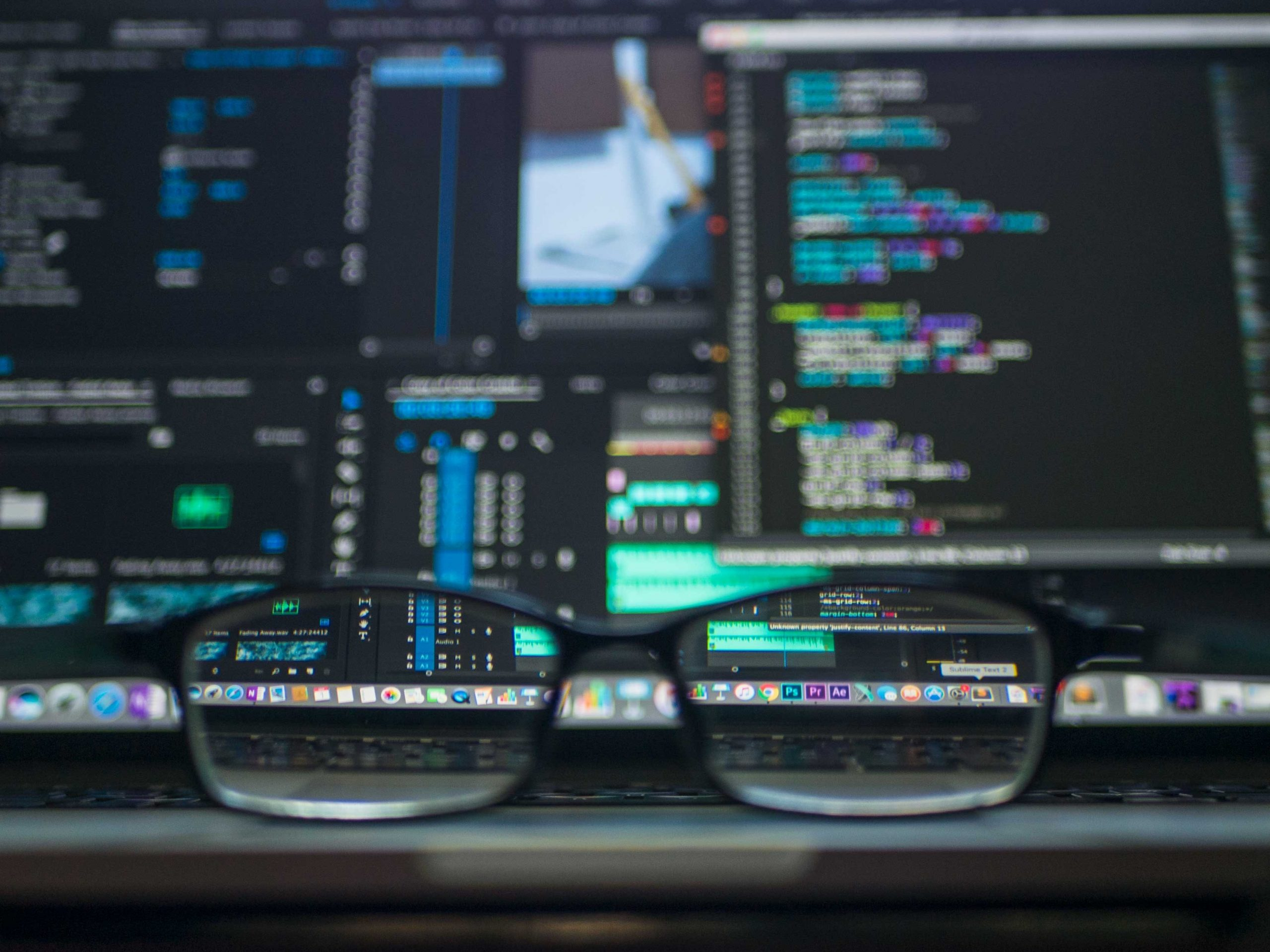 Glasses in front of a computer screen filled with code